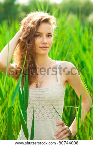 Portrait of beautiful young woman in green grass - stock photo