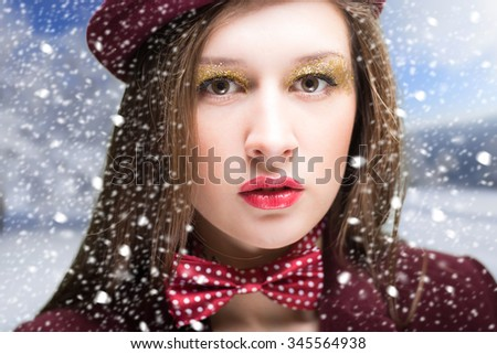 Portrait of beautiful young woman in hat and bow tie with red lips. Closeup of pretty girl with fancy make-up on winter snow blurred background.