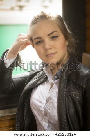 Portrait of beautiful young woman in leather jacket sitting in train at window - stock photo