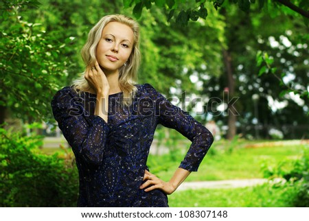Portrait of beautiful young woman in park - stock photo