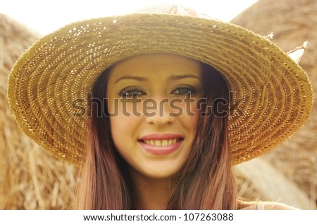 Portrait of beautiful young woman in sun hat - stock photo