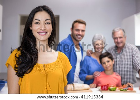 Portrait of beautiful young woman in the kitchen and other family member standing in background - stock photo