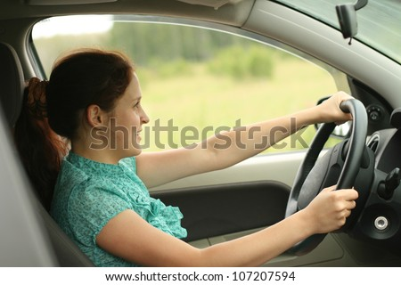 Portrait of beautiful young woman in the new car - outdoors - stock photo
