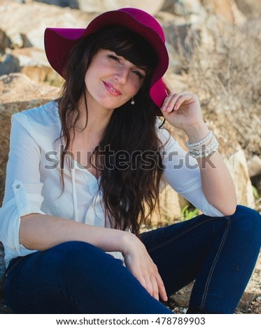 Portrait of beautiful young woman in the stones on the seashore