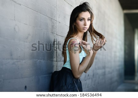 Portrait of beautiful young woman in urban background - stock photo