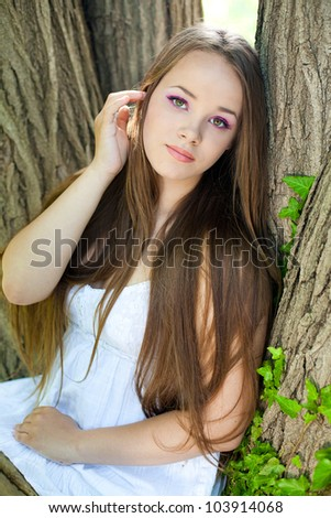 portrait of beautiful young  woman in white dress at park - stock photo