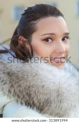 Portrait of beautiful young woman in white fur coat close up. - stock photo