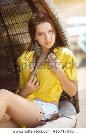 Portrait of beautiful young woman in yellow t-shirt and white shorts relaxing on chaise lounge near swimming pool  - stock photo