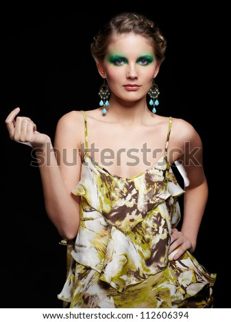 portrait of beautiful young woman ind summer dress with green and blue eye shade make up posing on black