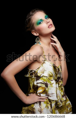 portrait of beautiful young woman ind summer dress with green and blue eye shade make up touching her neck