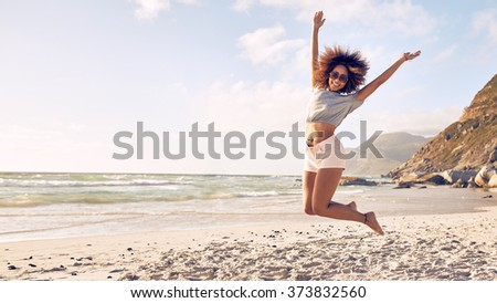 Portrait of beautiful young woman jumping in air at the beach. African female enjoying a summer day at the sea shore. - stock photo