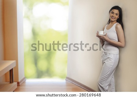 Portrait of beautiful young woman leaning on wall while holding cup of coffee - stock photo
