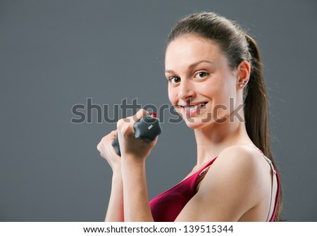 Portrait of beautiful young woman lifting dumbbells during exercise - stock photo