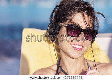 Portrait of beautiful young woman listening music on the pool