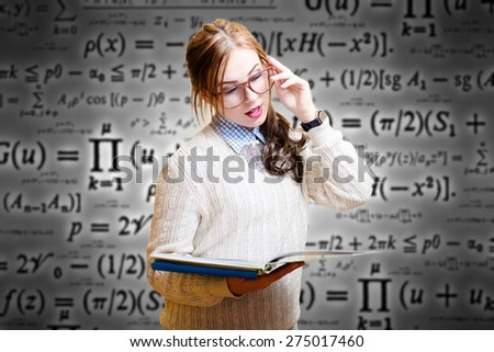 Portrait of beautiful young woman looking at book through glasses   - stock photo