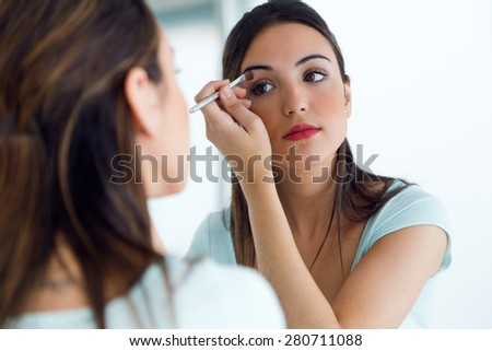 Portrait of beautiful young woman making make-up near mirror. - stock photo