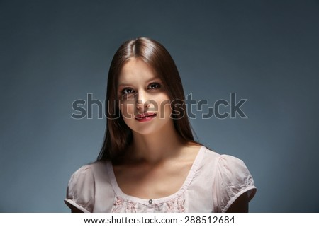 Portrait of beautiful young woman on dark background - stock photo