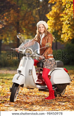 Portrait of beautiful young woman on scooter posing in the park - stock photo