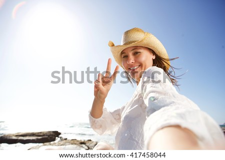 Portrait of beautiful young woman on vacation at the beach taking selfie and gesturing peace sign - stock photo