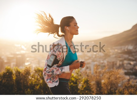 Portrait of beautiful young woman out for a run on a hot sunny day. Caucasian female model jogging outdoors. - stock photo