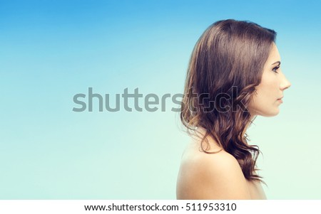 Portrait of beautiful young woman, over blue background, with copyspace for slogan or text message
