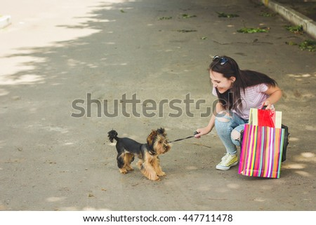 Portrait of beautiful young woman playing and walk with dog on the city street . Shopping with a dog - stock photo