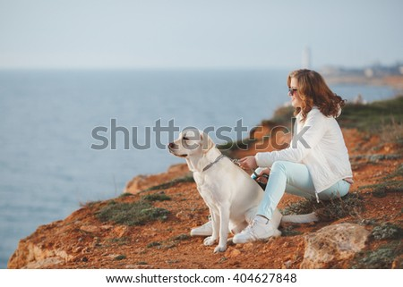 Portrait of beautiful young woman playing with dog on the sea shore. portrait of Young girl sitting on the ground with her dog retriever. woman with puppy. Girl with dog. - stock photo