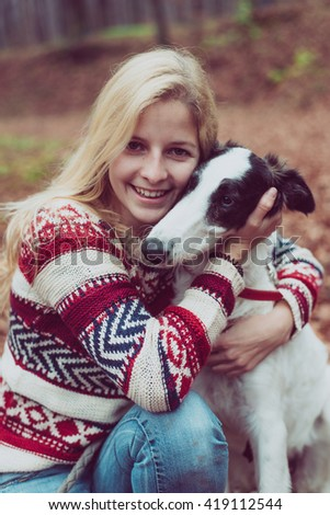 Portrait of beautiful young woman playing with dog outdoor. - stock photo