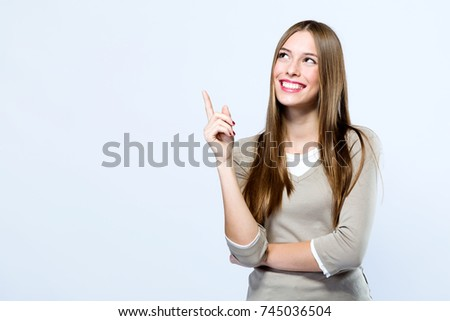 Portrait of beautiful young woman pointing up over white background.