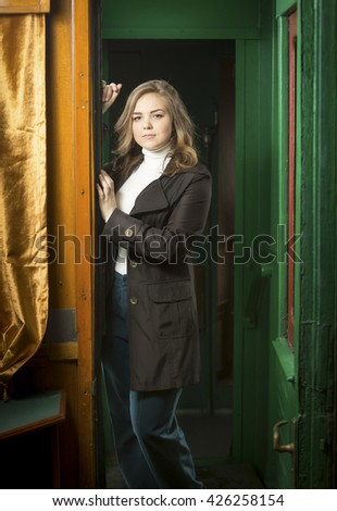 Portrait of beautiful young woman posing in retro train doorway - stock photo