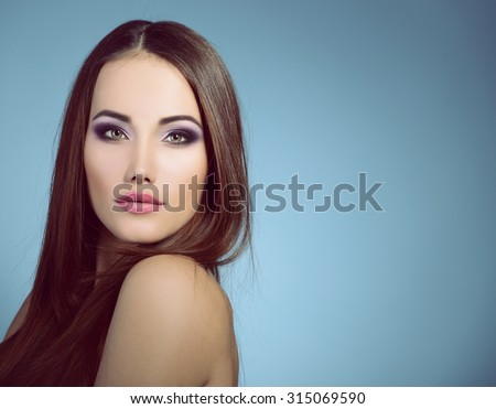 Portrait of beautiful young woman posing in studio, face close up. Image toned. - stock photo