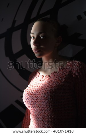 Portrait of beautiful young woman posing in the darkness - stock photo