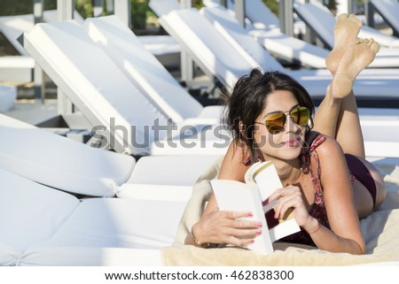 Portrait of beautiful young woman reading a book on the beach.Summer holiday
