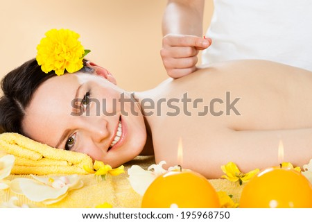 Portrait of beautiful young woman receiving acupuncture treatment in spa - stock photo