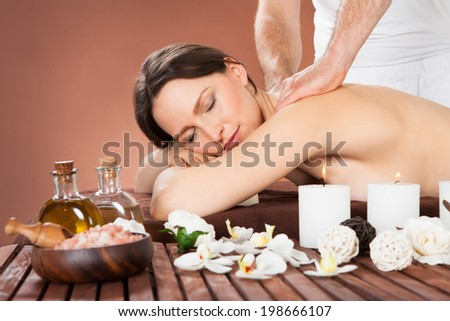 Portrait of beautiful young woman receiving back massaging in spa