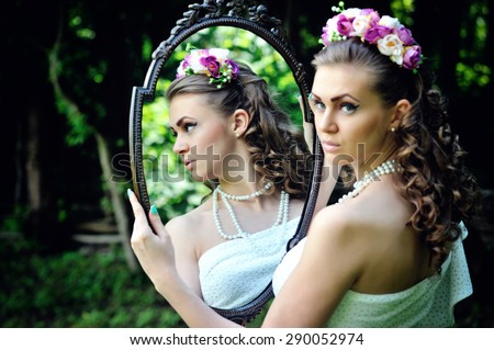 Portrait of beautiful young woman reflected in mirror - stock photo