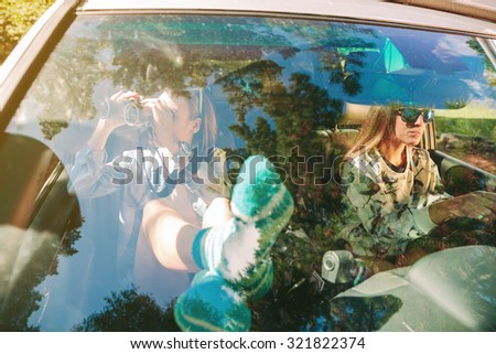 Portrait of beautiful young woman relaxing and looking through the binoculars  while her friend driving in a road trip adventure. Female friendship and leisure time concept. - stock photo