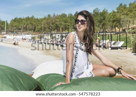 portrait of beautiful young woman relaxing on a big pillows on the beach.Summer holiday