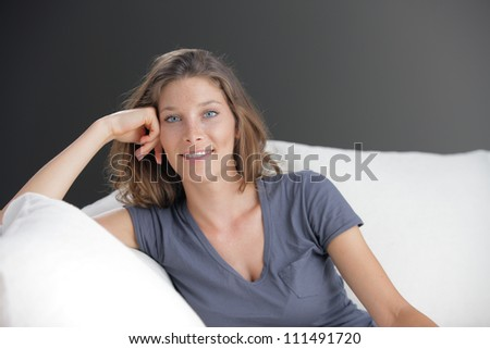 Portrait of beautiful young woman relaxing on couch - stock photo