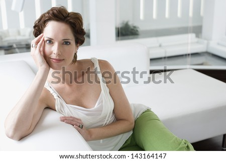 Portrait of beautiful young woman relaxing on sofa in living room