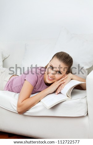 Portrait of beautiful young woman relaxing on sofa with book