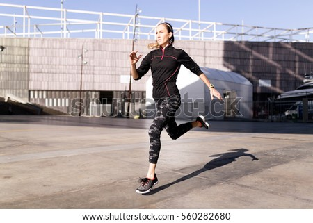 Portrait of beautiful young woman running in urban environment.
