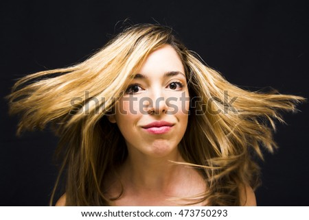 Portrait of Beautiful Young Woman Shaking Her Hair Over Black Background