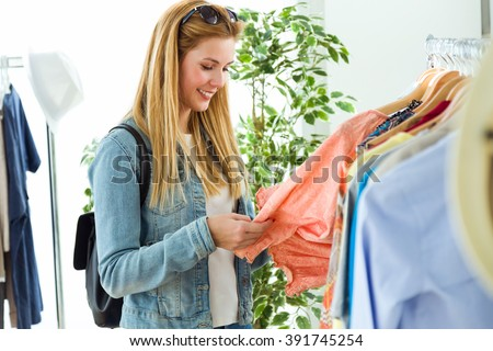 Portrait of beautiful young woman shopping in a clothes shop. - stock photo