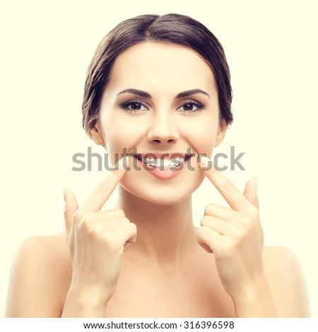 Portrait of beautiful young woman showing her smile or white teeth - stock photo