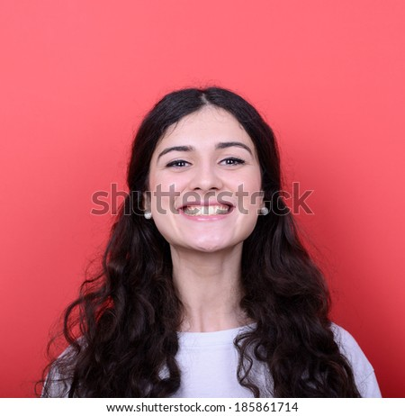 Portrait of beautiful young woman smiling against red background