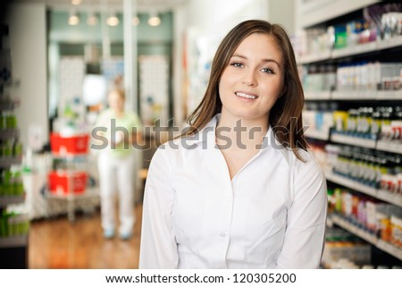 Portrait of beautiful young woman smiling at pharmacy - stock photo