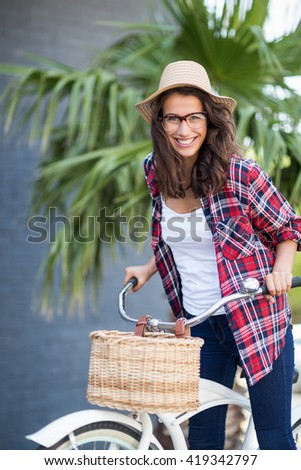 Portrait of beautiful young woman smiling riding a bicycle