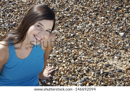 Portrait of beautiful young woman smiling while sitting at beach - stock photo