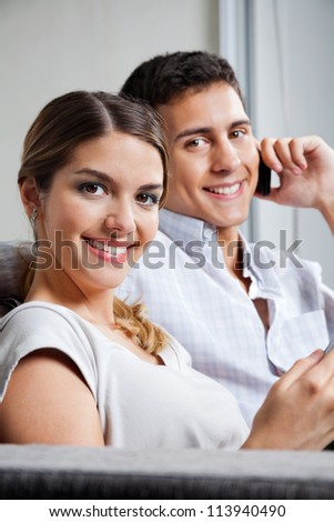 Portrait of beautiful young woman smiling with man on phone call - stock photo